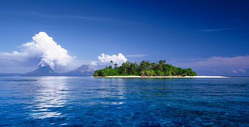An inviting tropical island surrounded by blue ocean.